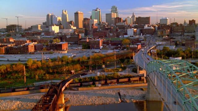 Aerial point of view over bridge over river toward Kansas City skyline at sunset / Missouri
