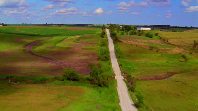 Aerial point of view over countryside with country road and house / Iowa