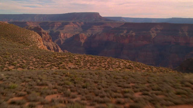 aerial point of view over desert brush and cliffs of grand canyon / arizona - arizona stock-videos und b-roll-filmmaterial