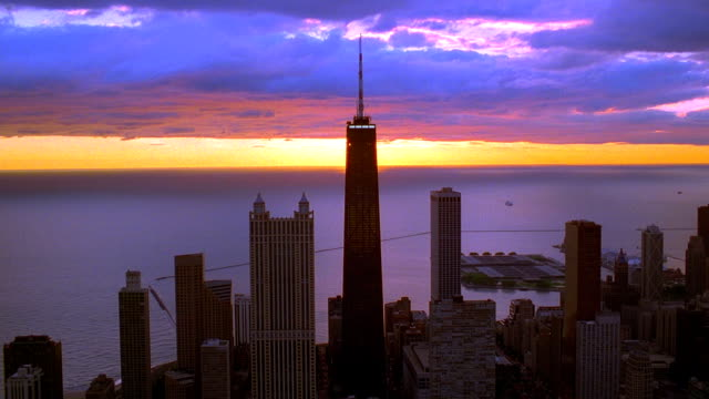 Aerial point of view over downtown Chicago and John Hancock Center with sunrise over Lake Michigan in background