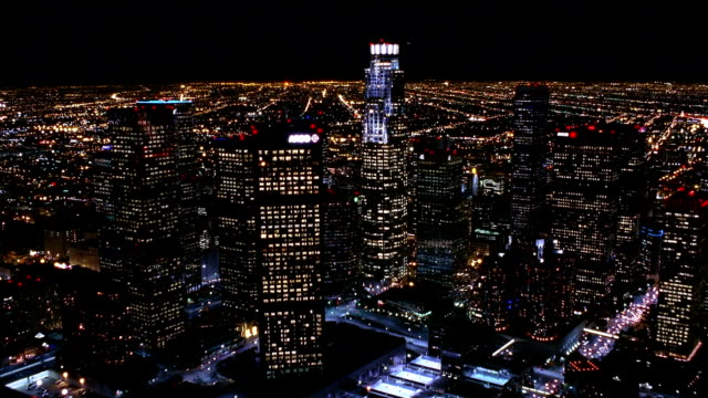 Aerial point of view over downtown Los Angeles and around Library Tower at night / Los Angeles