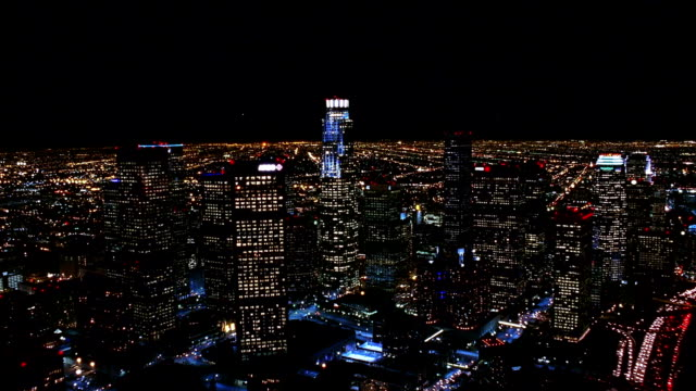 Aerial point of view over downtown Los Angeles and past Library Tower at night / California