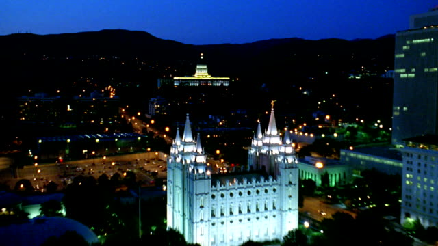 Aerial point of view over downtown Salt Lake City at night with Mormon Temple and capitol lit up / Utah