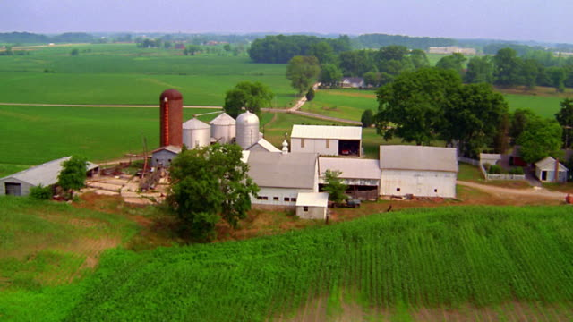 aerial point of view over farm with silos and fields / indiana - indiana stock videos & royalty-free footage