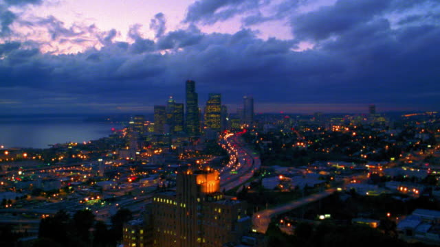 Aerial point of view over highway with traffic toward and over downtown Seattle at dusk / Washington