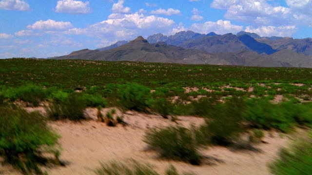 aerial point of view over hilly desert covered with brush / mountains in background / texas - セージブラッシュ点の映像素材/bロール