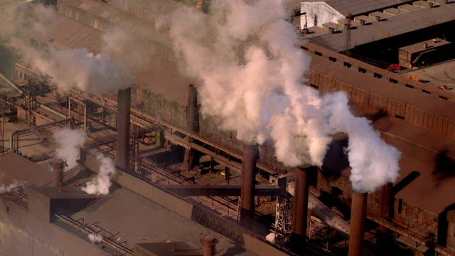 Aerial point of view over industrial factory with smokestacks emitting smoke / Baltimore, Maryland