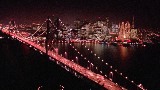 aerial point of view over lit bay bridge with traffic then towards san francisco skyline at night / california - baia di san francisco video stock e b–roll