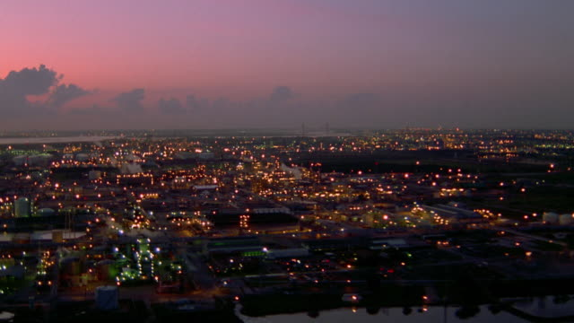 Aerial point of view over lit factories and refineries at dusk / Houston, Texas