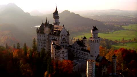 stockvideo's en b-roll-footage met aerial point of view over neuschwanstein castle on hilltop in autumn / bavaria, germany - beieren