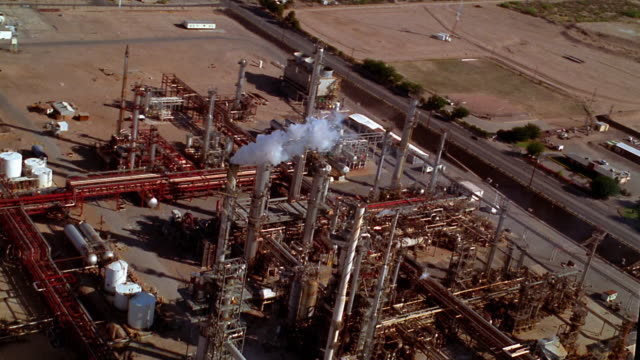 vidéos et rushes de aerial point of view over refinery with smokestacks and suburban area in background / el paso, texas - industrie du pétrole
