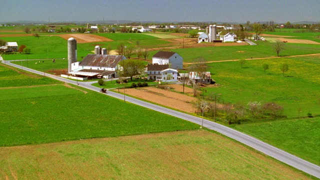 Aerial point of view over rural road with zoom in to Amish horse and buggy next to farm / Smoketown, Pennsylvania