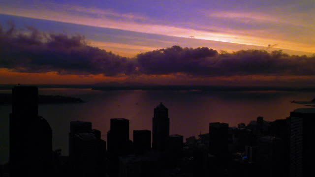 Aerial point of view over silhouetted downtown Seattle then low over water at sunset/rise with clouds / Washington