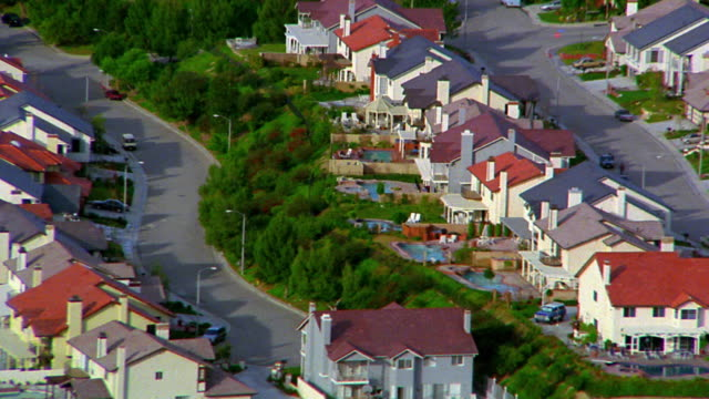 aerial point of view over suburban houses with pools / zoom out to reveal wide shot highway in foreground / san fernando valley - tract housing stock videos & royalty-free footage