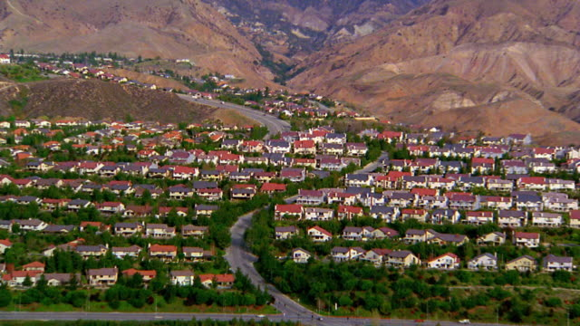 aerial point of view over suburban houses / zoom out to reveal wide shot mountains in background / zoom in / san fernando valley - tract housing stock videos & royalty-free footage