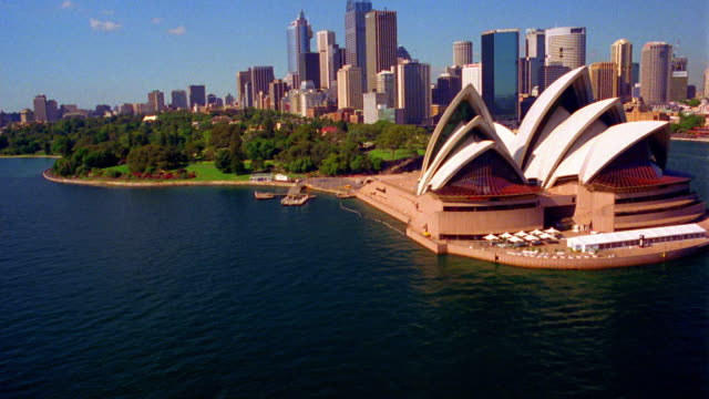 aerial point of view over sydney harbor and past opera house with downtown in background / australia - オペラ座点の映像素材/bロール