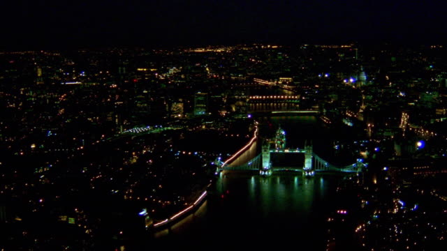 aerial point of view over tower bridge and along thames river at night / london - river thames stock videos & royalty-free footage