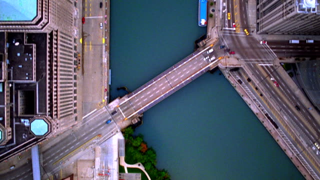 Aerial point of view over Wacker Drive and Chicago River with bridges + buildings / Illinois