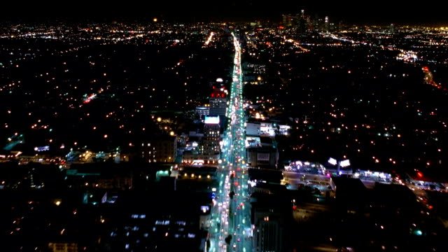 aerial point of view over wilshire boulevard with buildings and traffic at night / los angeles - ビバリーヒルズ点の映像素材/bロール