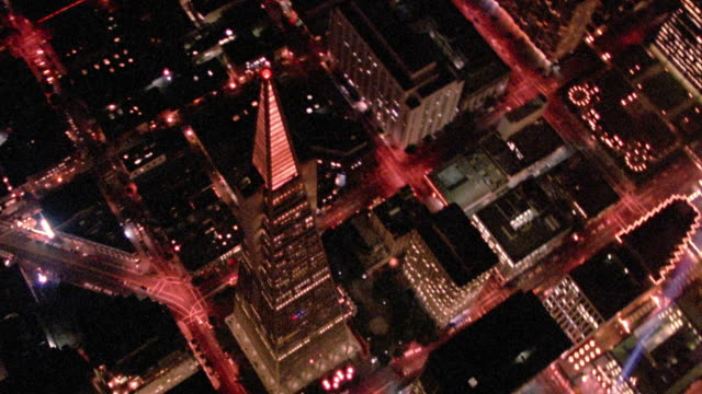 vídeos y material grabado en eventos de stock de aerial point of view overhead buildings in downtown san francisco with searchlight / rear point of view away - pirámide transamerica san francisco
