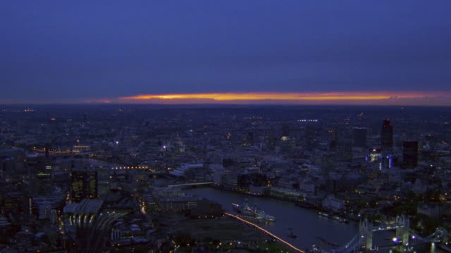 Aerial point of view past Tower Bridge and skyline at dusk / London