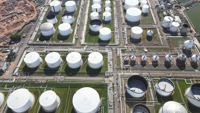 空中視点は、東南アジアの日の出時に石油・ガス精製工場の石油タンクと原油産業および石油化学産業背景を撮影しました - 石油点の映像素材/bロール