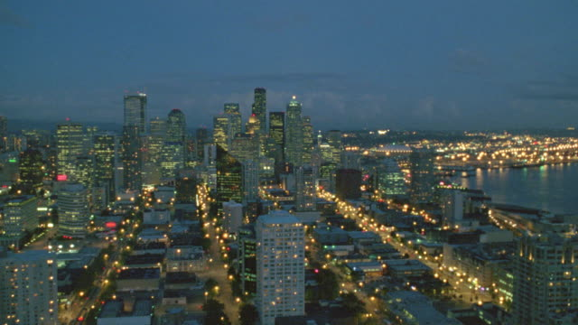 Aerial point of view toward and past Space Needle then over downtown Seattle to Kingdome at night / Washington