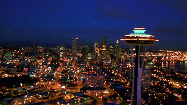 Aerial point of view toward and past Space Needle then toward downtown Seattle at night / Washington