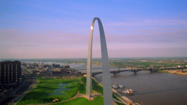 Aerial point of view toward and tilt down to overhead close up Gateway Arch next to Mississippi River / St. Louis, Missouri