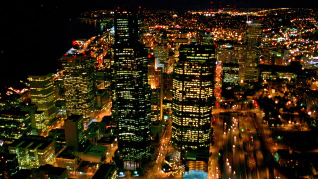 aerial point of view toward downtown seattle to overhead buildings and streets at night / washington - washington mutual tower stock videos & royalty-free footage