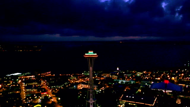 Aerial point of view toward Space Needle to overhead around it at night / Seattle, Washington