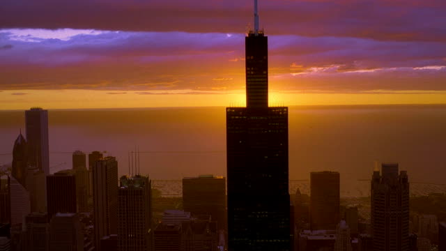 Aerial point of view towards and around Sears Tower with dawn over Lake Michigan in background / Chicago, Illinois