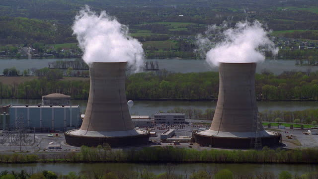 aerial point of view two cooling towers emitting steam at a nuclear power plant - emitting stock videos & royalty-free footage