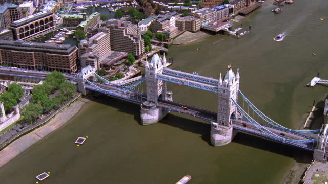 Aerial point of view wide shot around Tower Bridge with boats on Thames River / London