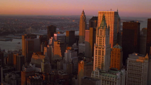 aerial point of view wide shot moving east over skyscrapers in lower manhattan at dusk / nyc - woolworth building stock videos & royalty-free footage