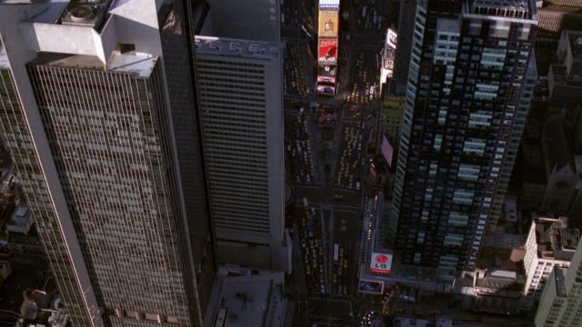 aerial point of view wide shot neon signs in times square zoom out zoom in overhead skyscrapers, traffic and island / nyc - 1998 stock videos & royalty-free footage