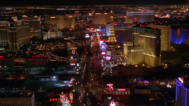 Aerial point of view wide shot over Las Vegas Boulevard at night, passing various casinos / Nevada