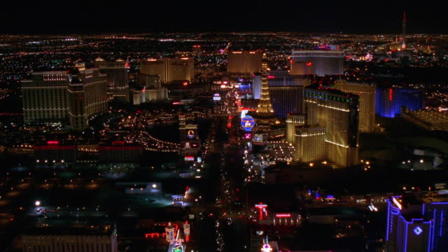 Aerial point of view wide shot over Las Vegas Boulevard, passing various casinos at night and circling Stratosphere