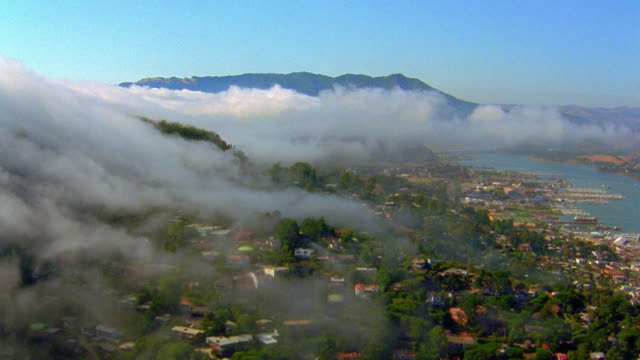 Aerial point of view wide shot over residential neighborhood on hills with low rolling fog or clouds near San Francisco, California