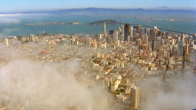 vídeos y material grabado en eventos de stock de aerial point of view wide shot over san francisco cityscape to downtown and transamerica pyramid with clouds/fog - pirámide transamerica san francisco