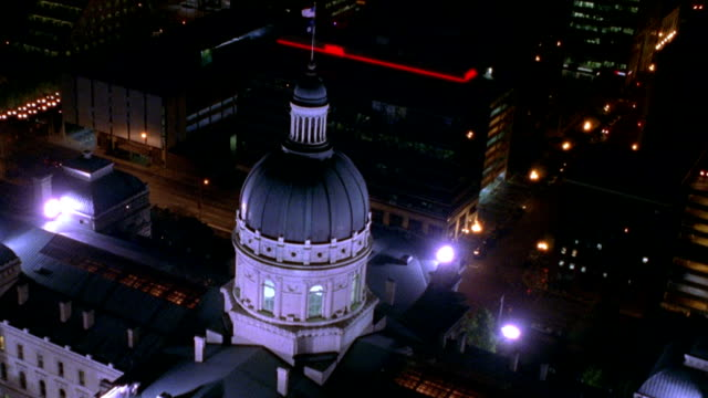 vídeos de stock, filmes e b-roll de aerial point of view zoom in over state capital building and downtown indianapolis at night / indiana - capitólio estatal