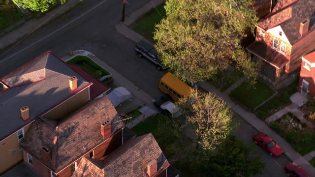 aerial point of view zoom in zoom out over suburban street with school bus driving on it / pittsburgh, pennsylvania - pittsburgh video stock e b–roll