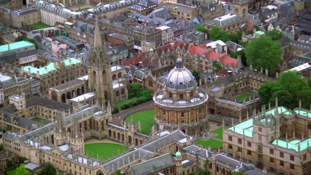 aerial point of view zoom out and zoom in over radcliffe camera library + st. mary's church at oxford university / england - oxford england stock videos & royalty-free footage