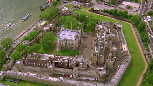 aerial point of view zoom out around tower of london with zoom in british flag flying from roof / london - tower of london stock videos and b-roll footage