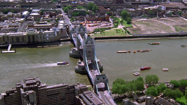 aerial point of view zoom out around traffic crossing tower bridge with boats on thames river / london - tower bridge stock-videos und b-roll-filmmaterial
