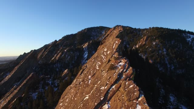 aerial: pointy, tree covered mountains in evening sun - kirchturmspitze stock-videos und b-roll-filmmaterial