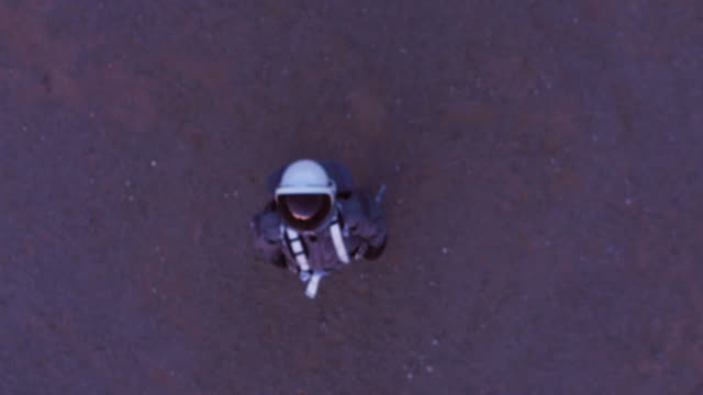 Aerial portrait zoom out of astronaut in space suit