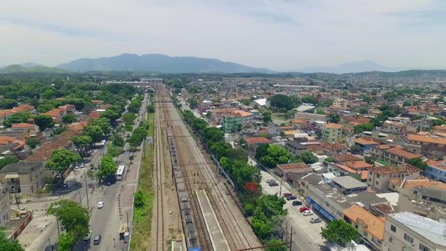 vídeos de stock, filmes e b-roll de aerial, pov, a train goes through rio de janeiro's suburbs, brazil - distrito