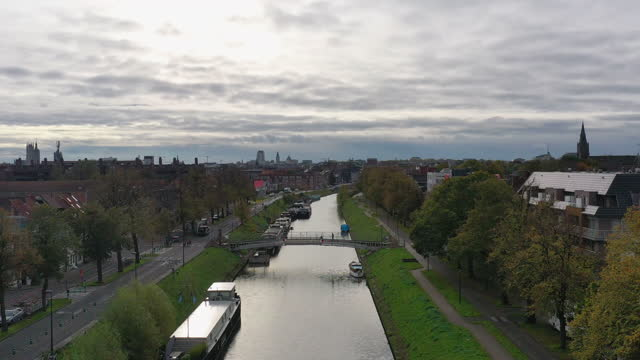 aerial, pov, a treelined canal and gent cityscape, belgium - overcast stock videos & royalty-free footage
