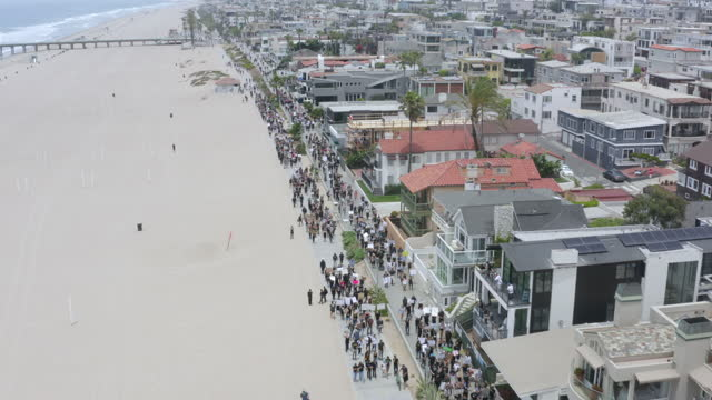 aerial: protesters wield signs march along beach walkway under houses and palm trees - manhattan beach, california - unfairness stock videos & royalty-free footage